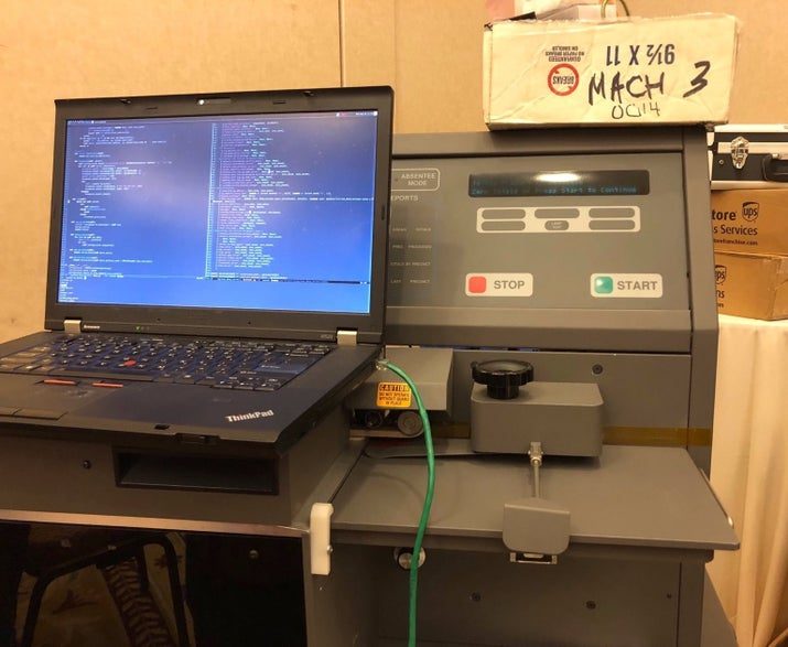 A hacker's laptop hooked up to an ES&S M650 Optical Scan Tabulator.
