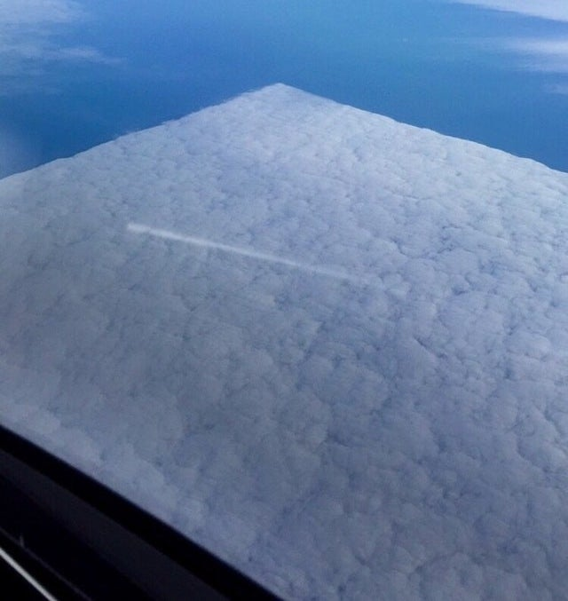 A perfectly square-shaped area of clouds seen from above, from a plane window