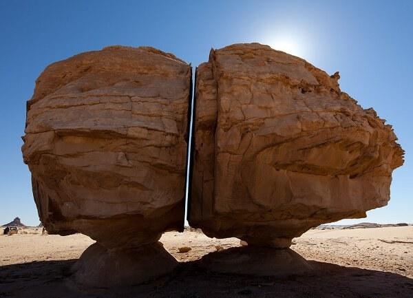 A very large rock formation that is split perfectly down the middle, in a straight line only a few inches wide