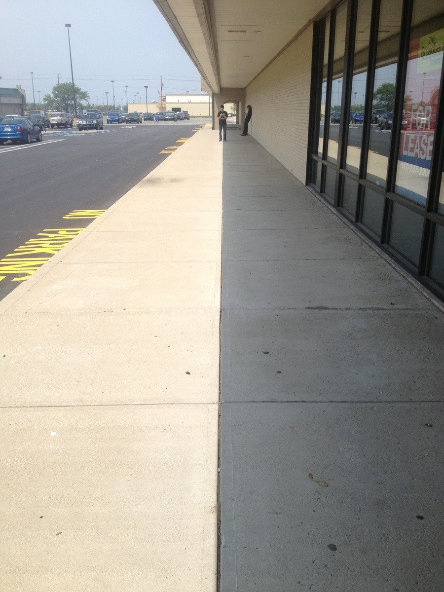A sidewalk half-covered in shade, forming a perfect line down the middle that lines up with the sidewalk's crack