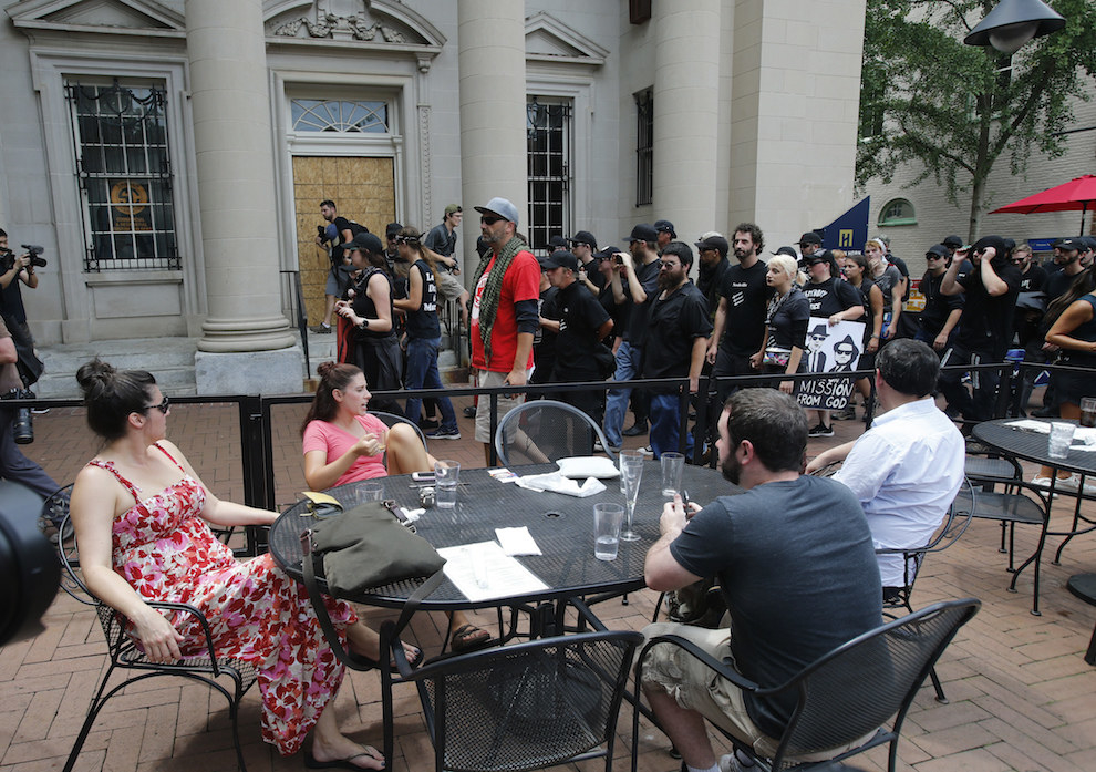 A group, Anti-fascism demonstrators, march past lunchtime diners in the downtown area in anticipation of the anniversary of last year's Unite the Right rally in Charlottesville.