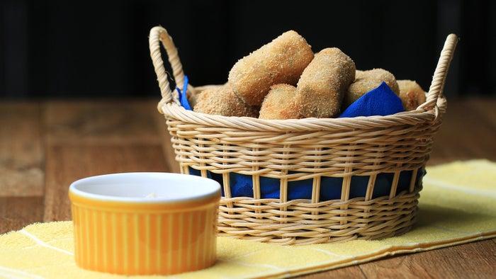 Rendimento: 28 croquetesVocê vai precisar de:1 kg de batatas descascadas (5 média)1 xícara de atum em conserva¾ xícara de queijo muçarela ralada¾ xícara de salsinha picadaSal a gostoPimenta do reino a gosto1 xícara de farinha de trigo3 ovos batidos1 xícara de farinha de rosca Óleo, para fritarMolho:5 colheres de sopa maionese1 colheres de sopa vinagre branco1 colheres de sopa de açúcar2 colheres de sopa de cebola roxa picada1 colheres de sopa de azeite2 colheres de sopa de salsaSal a gostoPimenta do reino a gostoModo de preparo:1. Numa tigela média adicione as batatas, cubra com plástico filme e leve ao micro-ondas entre 8-12 minutos até ficarem macias. Deixe esfriar cerca de 5 minutos.2. Numa tigela pequena, adicione a maionese, o vinagre, o açúcar, a cebola, o azeite, o sal e a pimenta. Misture até ficar homogêneo e reserve.3. Amasse as batatas até que não haja nenhum pedaço grande.4. Adicione o atum, o queijo, salsinha, o sal e a pimenta. Mexa até que esteja tudo bem incorporado e modele a mistura de batata em cilindros de 5 cm.5. Passe os croquetes na farinha, depois passe nos ovos e depois cubra-os de forma homogênea com a farinha de pão.6. Aqueça óleo em uma panela funda a 180°C.7. Frite 2-3 croquetes por vez até ficarem dourados, depois retire o excesso de óleo em um prato forrado com papel toalha.8. Sirva com o molho.9. Aproveite!