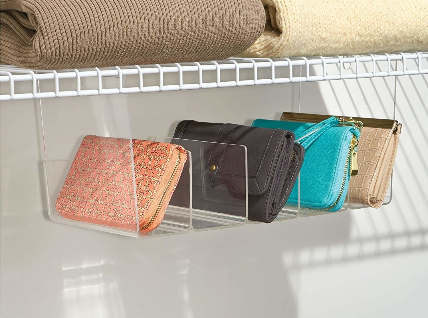 small clear shelf attached to the bottom of a wire shelf with five slots big enough to fit wallets and small purses