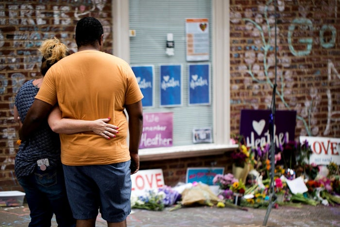 A couple embraces as they observe the flowers and handwritten messages at a makeshift memorial dedicated to Heather Heyer in downtown Charlottesville, Virginia, on Aug. 12, one year after the violent white nationalist rally left Heyer dead and dozens injured.
