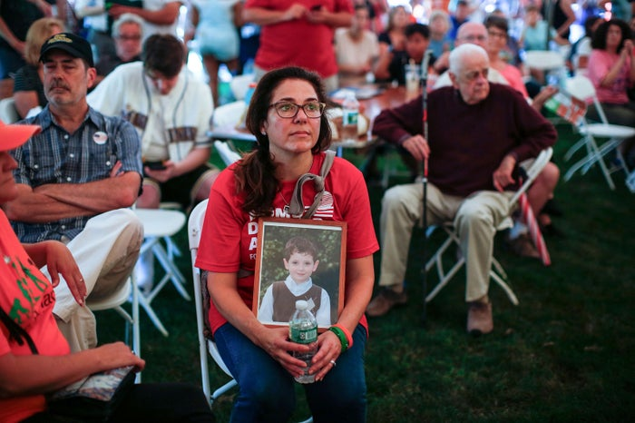 "Francine Wheeler displays a photograph of her son, Sandy Hook Elementary shooting victim Ben Wheeler, at the ""March for our Lives"" rally in Newtown, Connecticut, on Aug. 12."