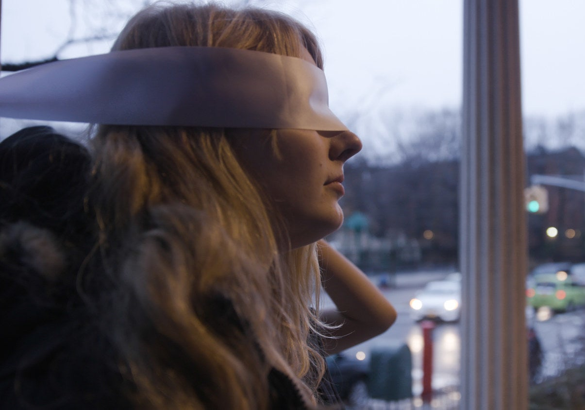 A Whisperlodge participant gets blindfolded before she's led into the building.