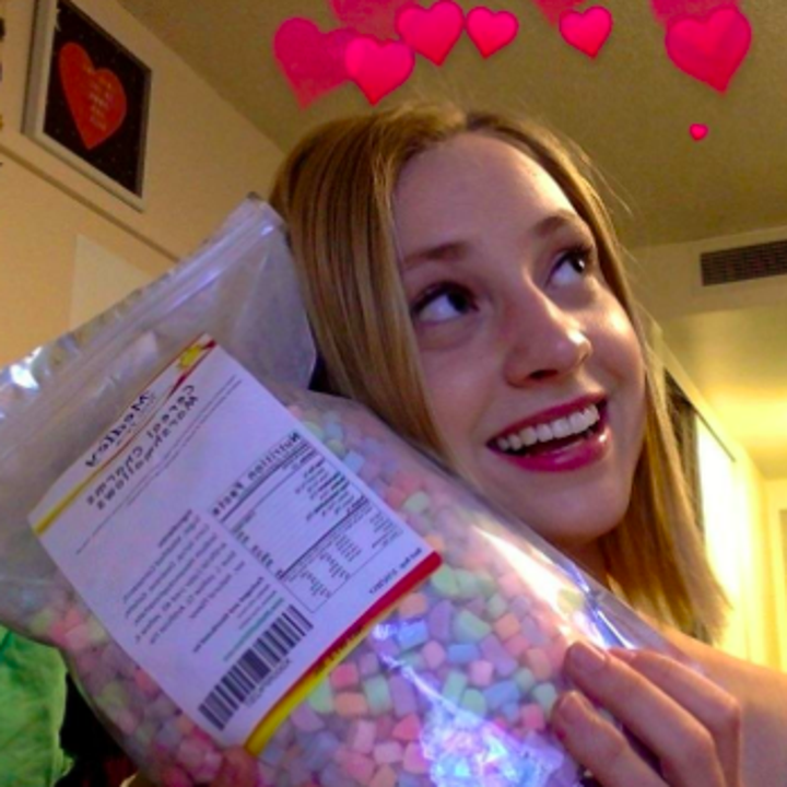 A reviewer holding up their bag of marshmallows with animated hearts over their head