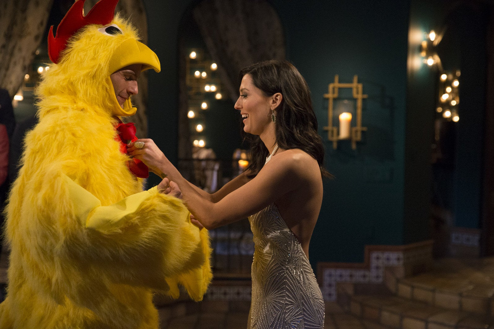 Becca gives a rose to David, who arrived wearing a chicken costume, during Episode 1.
