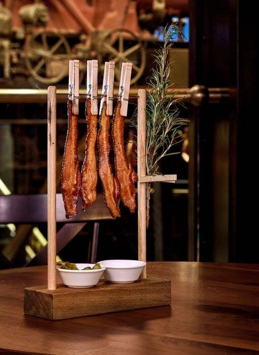 Location: The Edison, Disney Springs, Orlando, FloridaThis bacon dish is always a crowd pleaser! You get four thick-cut strips of bacon that are seasoned with maple and black pepper and rosemary, all of which is lightly torched before serving. Each clothesline is also served with a fruit mastarda dipping sauce and sweet and spicy pickles!