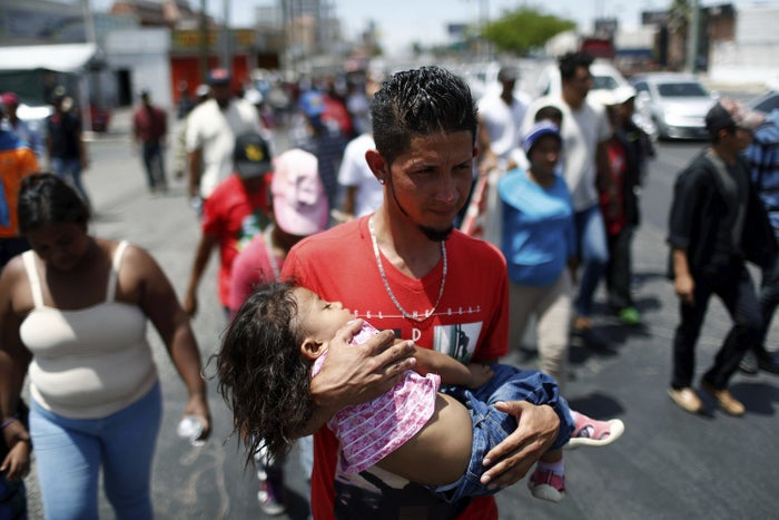 A Central American migrant traveling with the Stations of the Cross annual migrant caravan with a little girl in his arms, in Hermosillo, Mexico, on April 23, 2018.