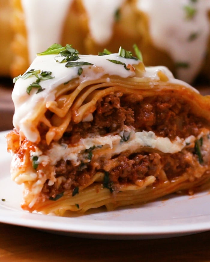 Servings: 10INGREDIENTS3 tablespoons olive oil, divided½ medium yellow onion, diced4 cloves garlic, minced1 pound ground beef1 teaspoon salt1 teaspoon black pepper15 ounces tomato sauce3 ounces tomato paste15 ounces (425 grams) ricotta cheese½ cup chopped fresh basil1 large egg½ cup shredded Parmesan cheese30 lasagna noodles, boiled until al dente, 2 cups shredded mozzarella cheeseBéchamel Sauce2 tablespoons unsalted butter2 tablespoons all-purpose flour1½ cups milk, hotSalt, to tasteFreshly ground pepper, to taste¼ cup shredded Parmesan cheeseChopped basil, for garnishShredded Parmesan cheese, for garnishPREPARATIONPreheat the oven to 375°F (190°C).Heat 2 tablespoons of olive oil in a large pot over high heat. Add the onion and garlic and cook until starting to brown, stirring occasionally, 3-4 minutes.Add the beef, salt, and pepper, and cook until all of the moisture has evaporated and the meat is starting to brown on the edges, breaking the meat up as you stir, 10-12 minutes.Add the tomato sauce and tomato paste, then reduce the heat to medium and bring the sauce to a simmer. Cook it down until the mixture becomes thick, about 15 minutes. Remove the pot from the heat and set aside.In a small bowl, combine the ricotta, basil, egg, and Parmesan. Stir until smooth. Set aside.Grease a large oven-safe metal bowl with the remaining tablespoon of olive oil, then lay about 25 lasagna noodles along the sides and bottom of the bowl, fanning them out in an overlapping pattern. The ends of the noodles should hang over the sides of the bowl.Slice the remaining lasagna noodles in half crosswise. These will serve as the layers between the meat and the cheese mixtures.Sprinkle half of the mozzarella into the bottom of the bowl on top of the noodles. This will help bind the noodles together when cooked. Spread half of the meat mixture evenly over the mozzarella, then lay half of the cut noodles over the sauce. Spread all of the ricotta mixture over the noodles, then layer with th