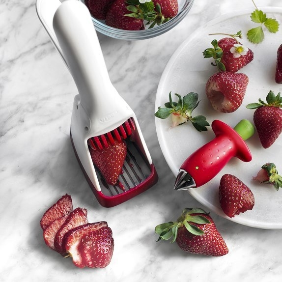 The tool slicing a strawberry that has been placed in the center of the small grate. The handles on the opposite end push together to slice the strawberry in one motion.