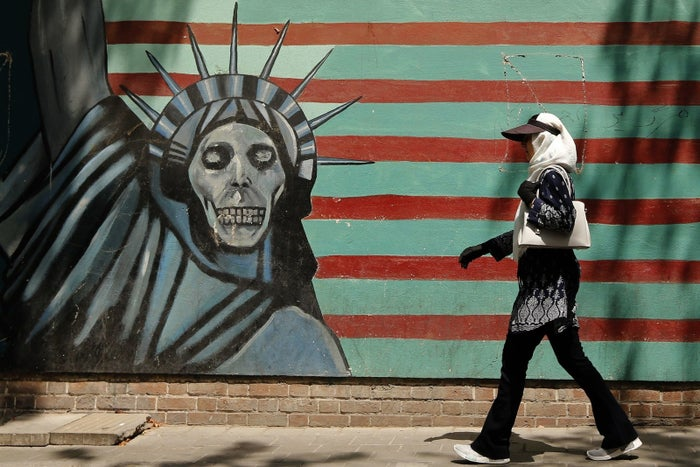 An Iranian woman walks past a mural depicting the Statue of Liberty with a dead face, painted on the wall of the former US embassy in Tehran on Aug. 7.