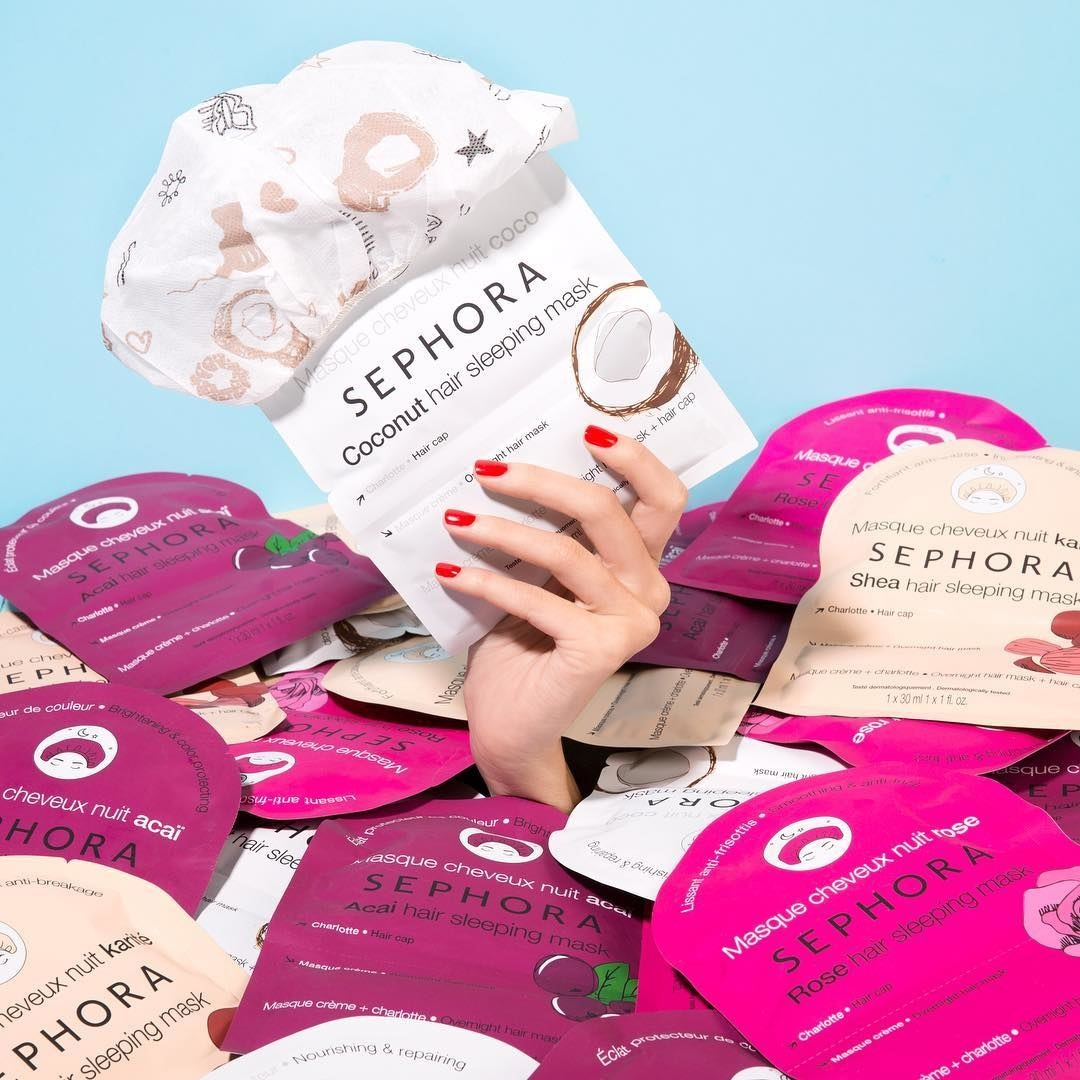 A pile of the masks, and a hand holding the coconut one with the cap resting on top