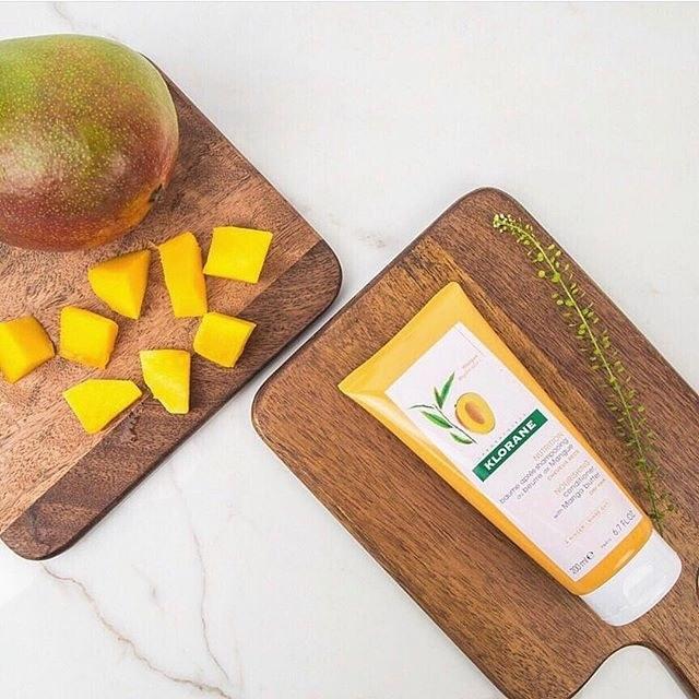 orange tube of hair product next to mango cubes