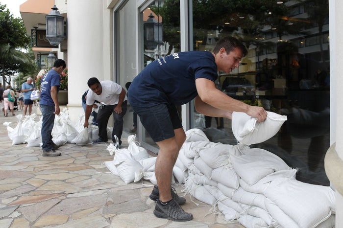 Austin Seawright (right) stacks sandbags in front of a closed store in preparation for Hurricane Lane on Thursday in Honolulu.
