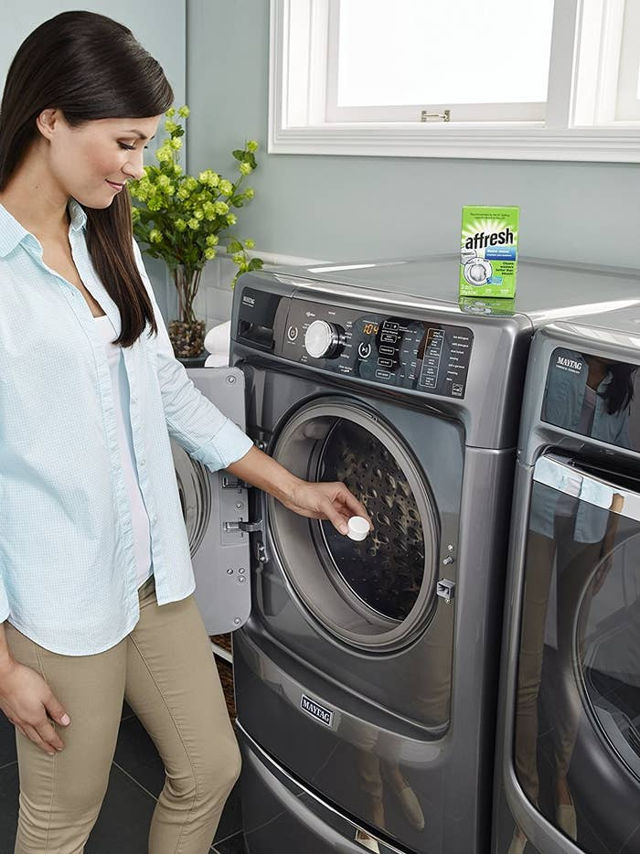 person putting a cleaning tablet into a front loading clothes washing machine