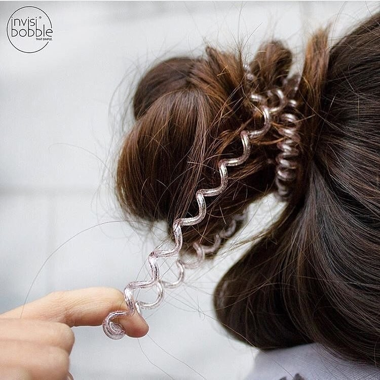 A hand pulling the  phone cord-like spiral tie from a bun