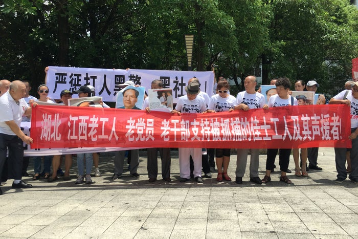 People hold banners at a demonstration in support of factory workers of Jasic Technology, outside the Yanziling police station in Pingshan District, Shenzhen, Guangdong Province, China, Aug. 6, 2018.