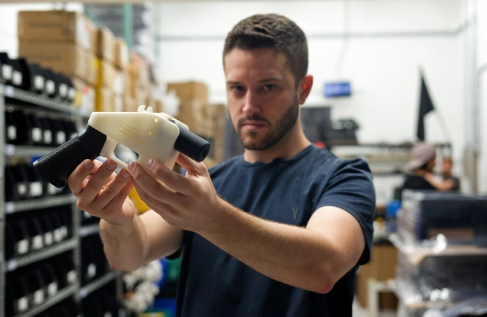"""Cody Wilson, owner of Defense Distributed, holds a 3D-printed gun called the """"Liberator."""""""