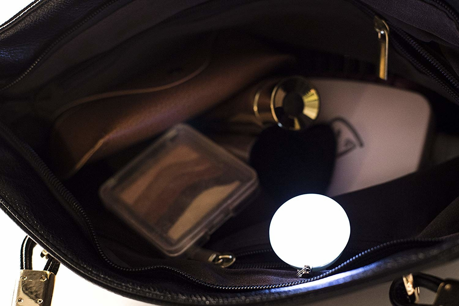 A small round light clipped onto the inside of a bag