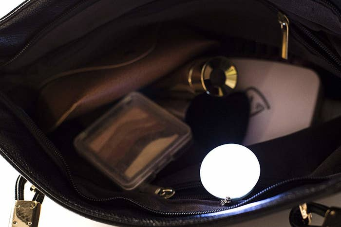 The bag light clipped to the inner pocket of a purse, lighting up the interior of the bag