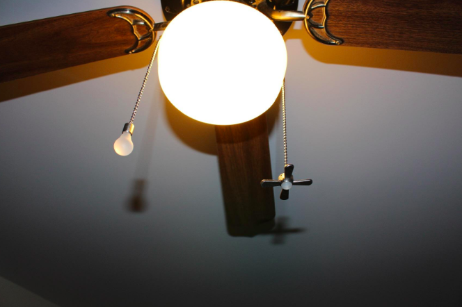 ceiling fan with chain charms that look like a lightbulb and fan