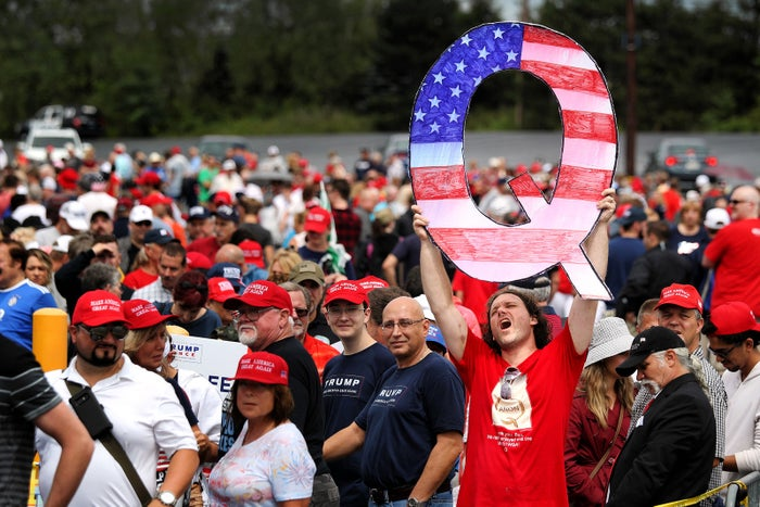 """David Reinert holds up a large """"Q"""" sign while waiting in line to see Trump at his rally on Aug. 2, in Wilkes-Barre. """"Q"""" represents QAnon, a conspiracy theory group that has been seen at recent rallies."""
