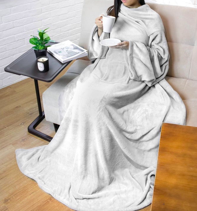 A person wearing the blanket with their arms through the sleeves while drinking a cup of tea