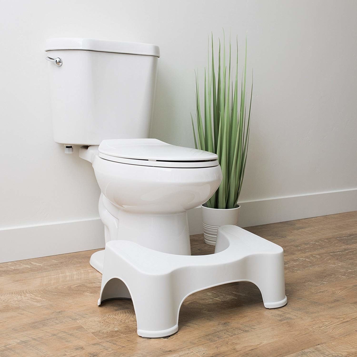A white stool that curves around your toilet tank to elevate your legs while using the bathroom
