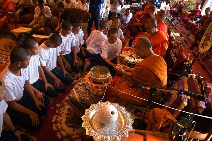 The boys bowed their heads and gave flower garlands to the monks of the Wat Phra That Doi Tung temple, and had sacred white thread wrapped around their wrists.