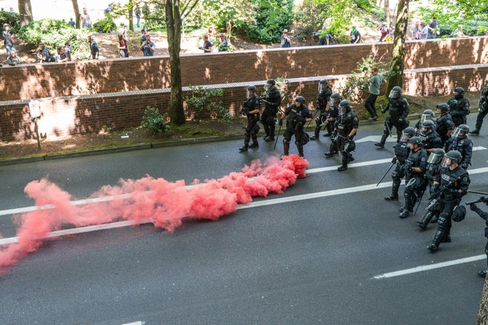 A smoke bomb thrown by left-wing counterprotesters rolls toward police.