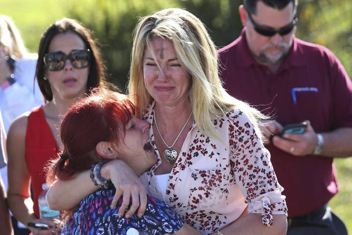 Parents wait for news after reports of a shooting at Marjory Stoneman Douglas High School in Parkland, Florida, on Wednesday, Feb. 14, 2018.