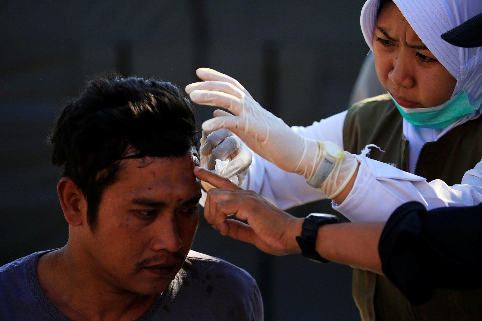 A paramedic treats an injured man outside the Tanjung hospital in Lombok Utara.