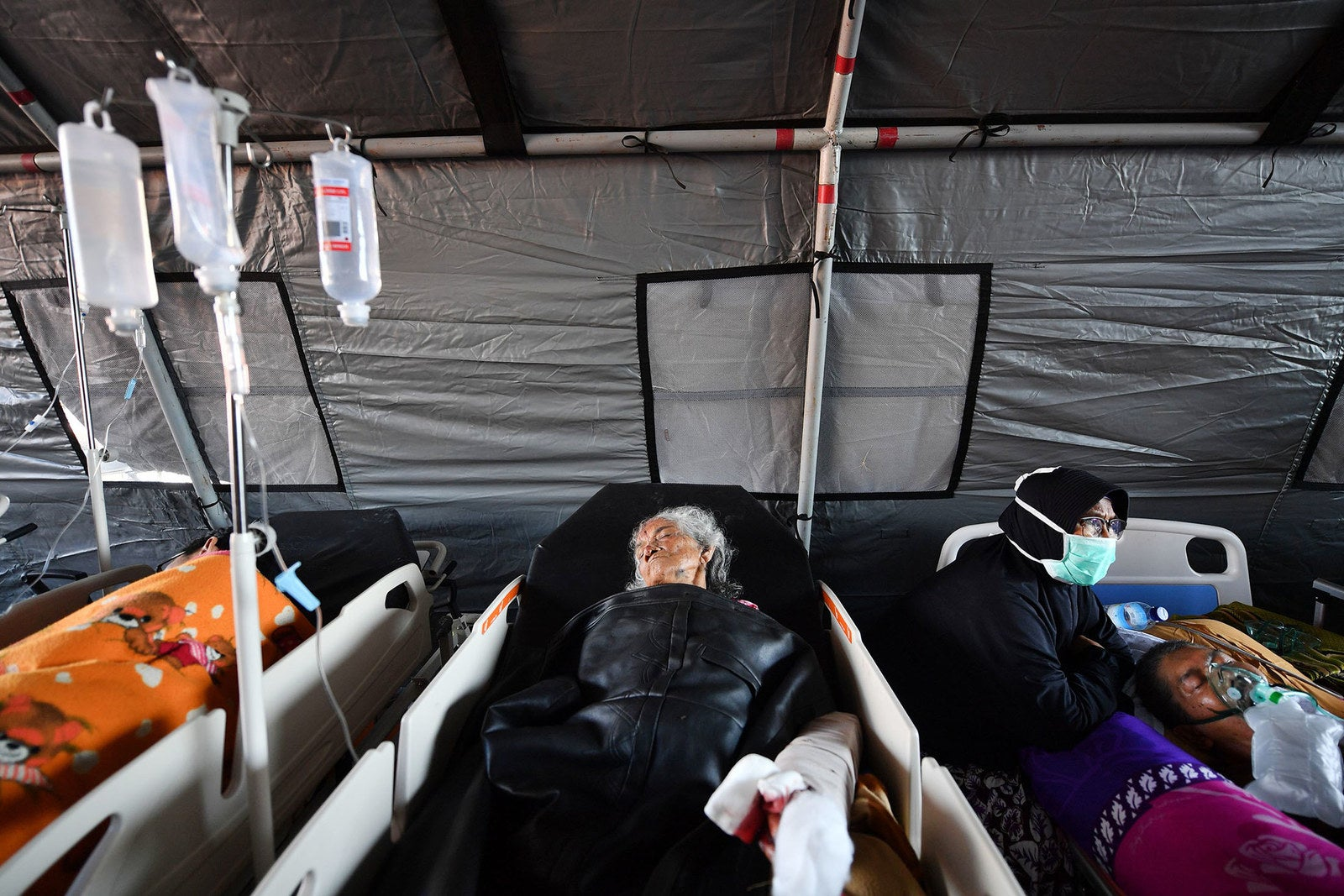 People lie in hospital beds at a makeshift ward set up outside the Moh Ruslan hospital in Mataram.
