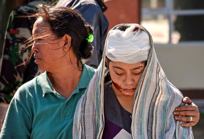 A woman injured during the earthquake walks outside North Lombok Hospital.