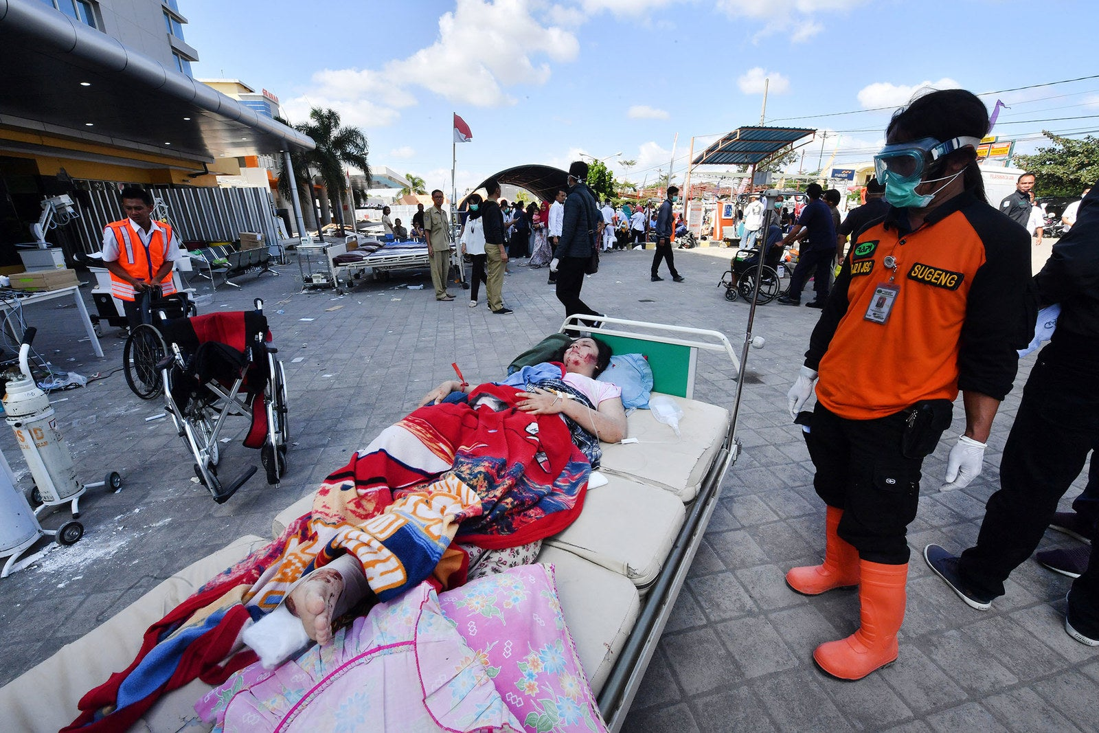 An injured earthquake victim waits for medical help outside the Moh Ruslan hospital in Mataram.