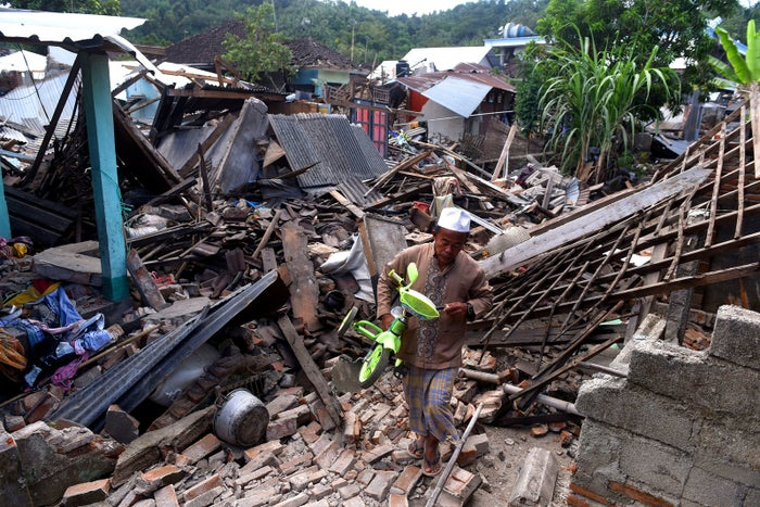A man carries a small tricycle through the ruins of houses damaged by an earthquake in West Lombok.