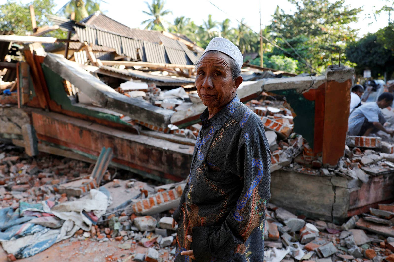 A villager walks through a collapsed house in Pemenang after the earthquake hit Lombok.