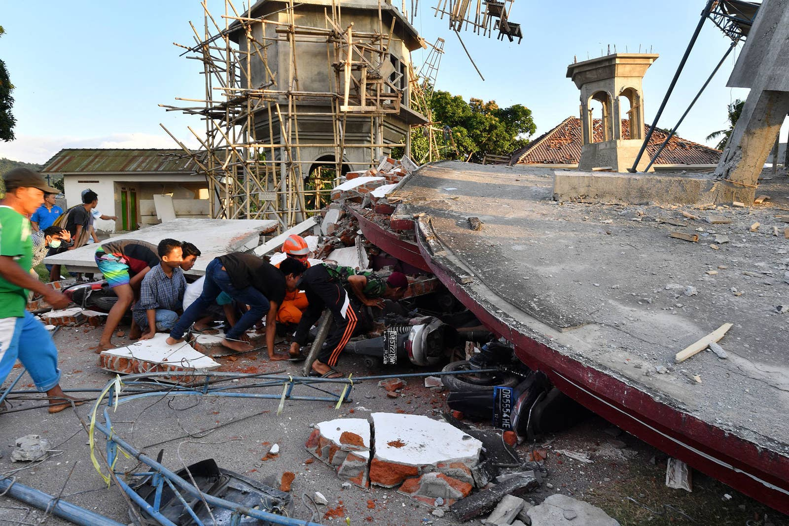 Residents and search and rescue personnel search for victims in the ruins of a mosque in Pemenang.