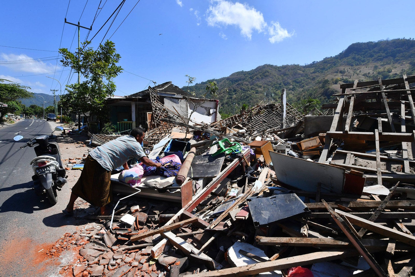 A villager salvages belongings from the ruins of a house in Pemenang.