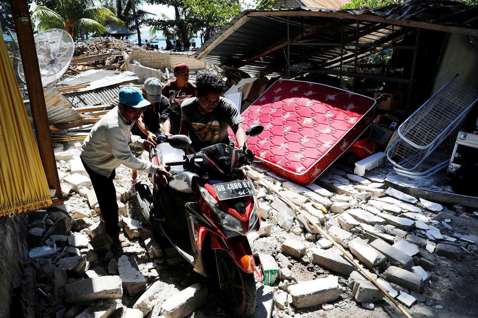 Villagers push a motorcycle through ruins in Pamenang.