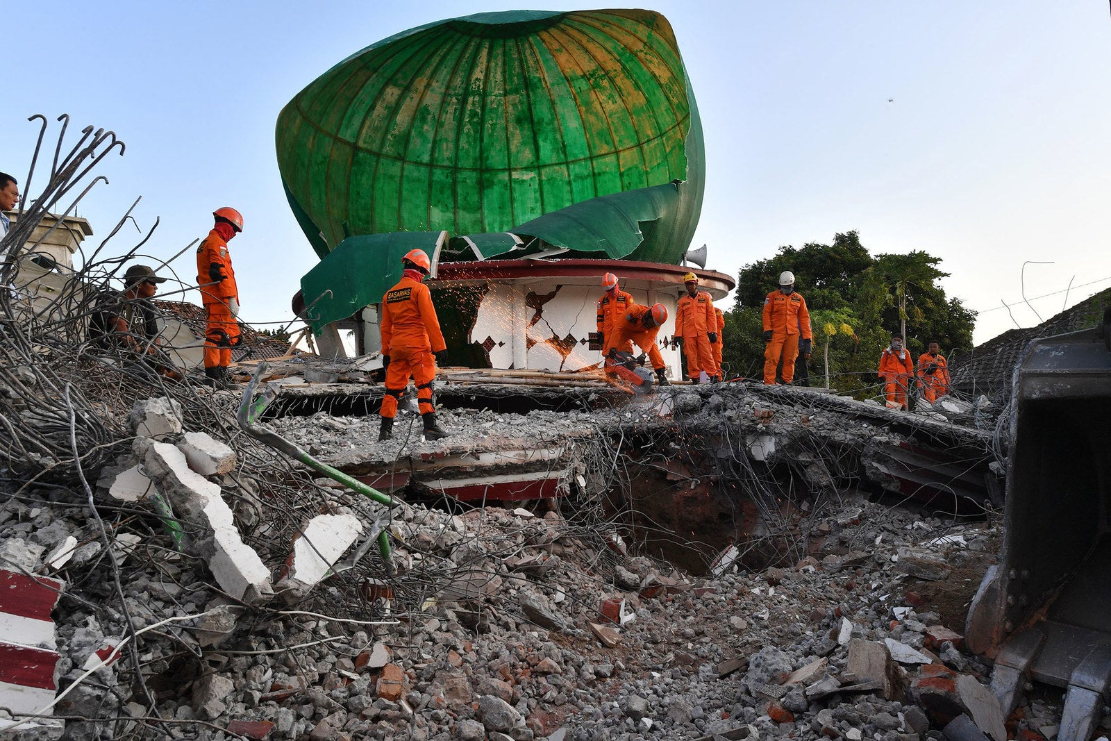 Indonesian search and rescue personnel work on a collapsed mosque in Pemenang, North Lombok, on Aug. 6, 2018.