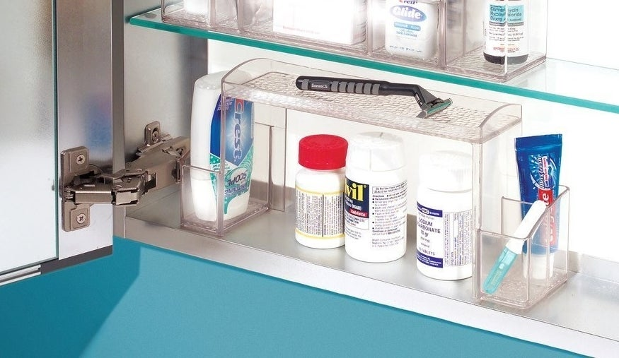 The inside a medicine cabinet with clear storage organizer in the shape of a U, with holders on each arm, holding tooth paste, and a shelf across the top holding a razor, while bottles of Advil and medicine sit on the cabinet under the shelf