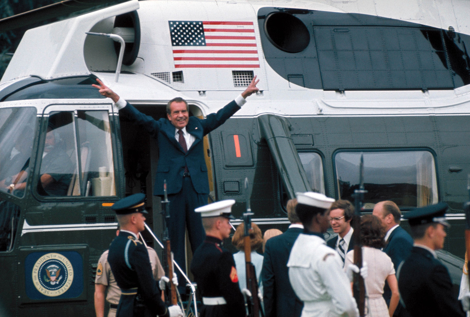 Nixon raises his hands with victory signs in the doorway of a helicopter after leaving the White House following his resignation on Aug. 9, 1974.