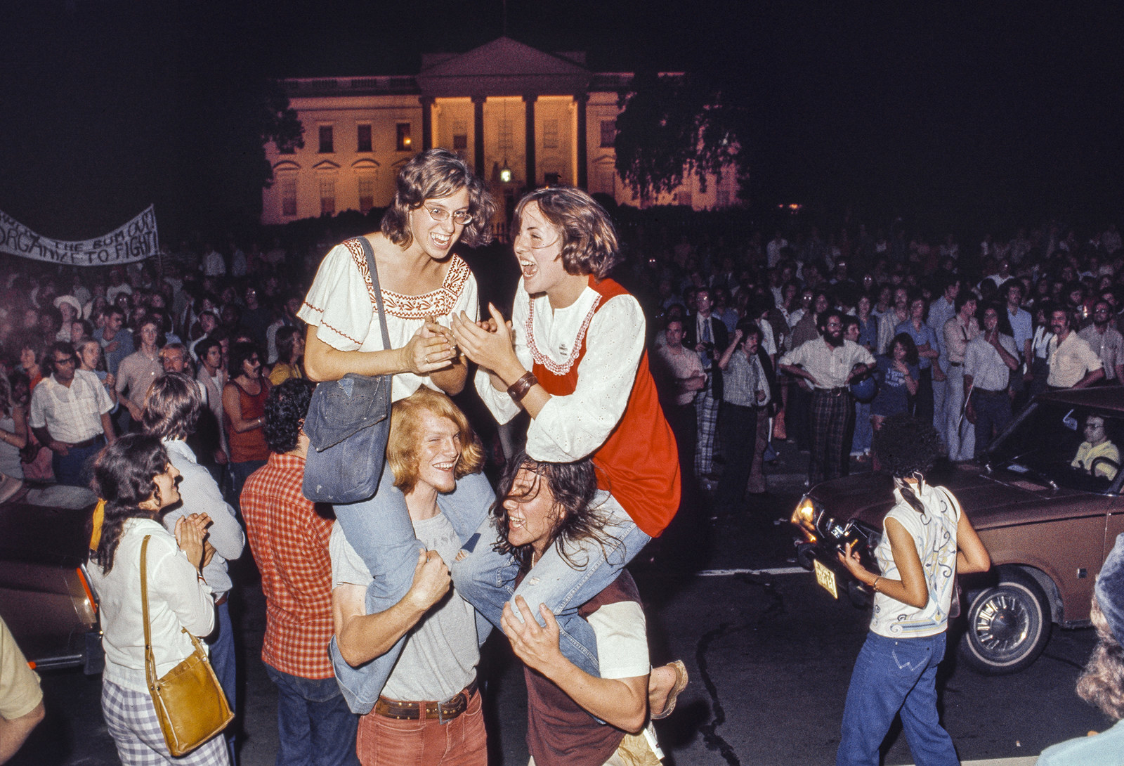 People celebrate in front of the White House on the evening of Nixon's resignation speech.