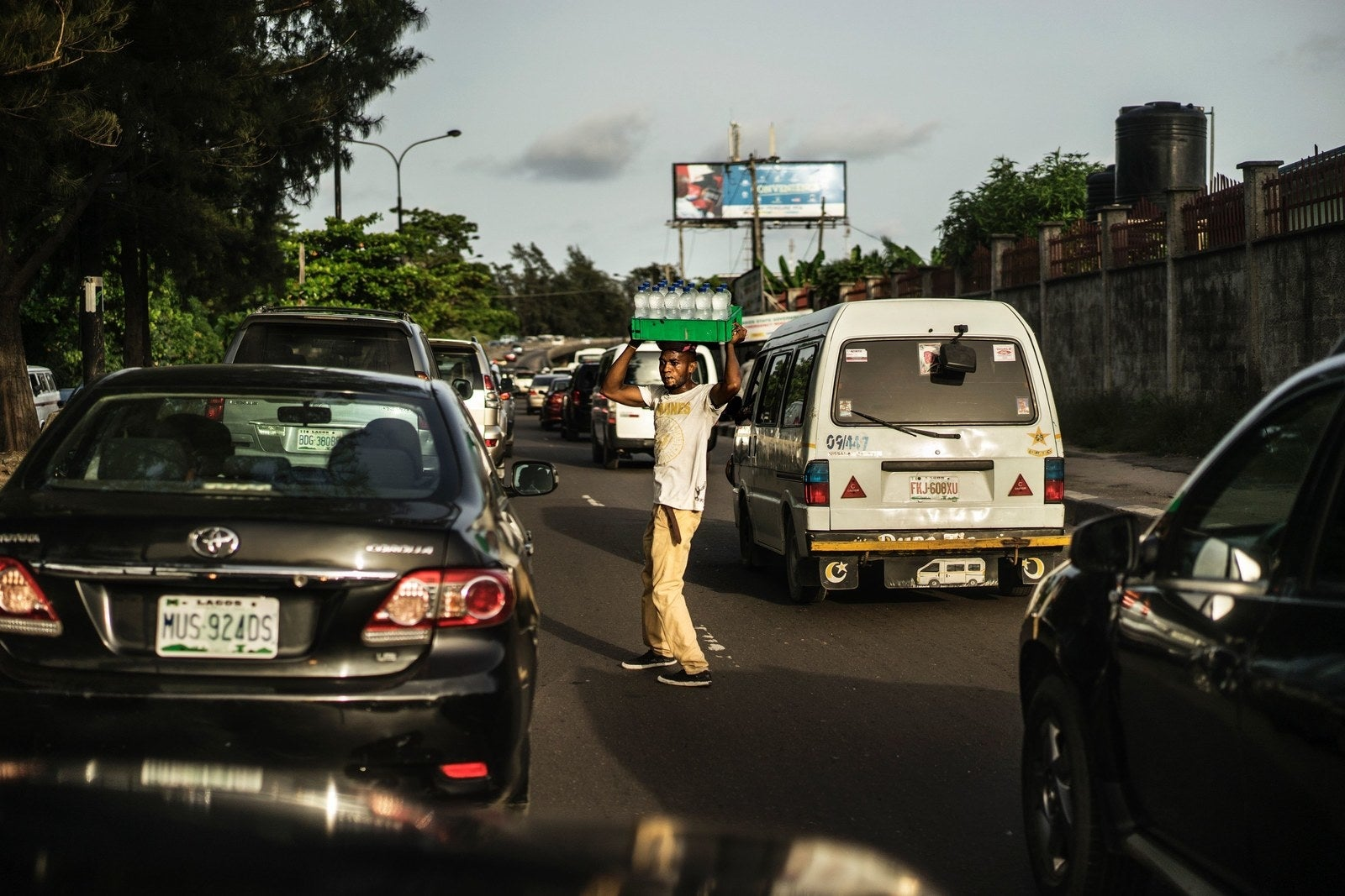 A hawker sells water bottles on a busy thoroughfare in Lagos.