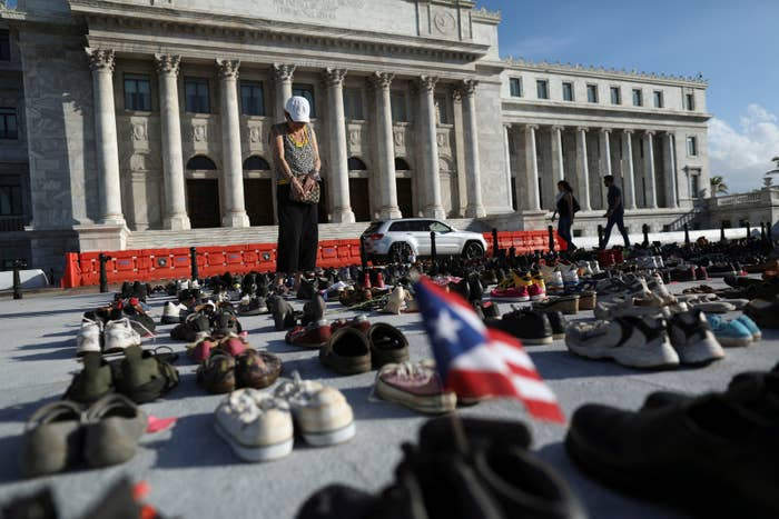 A woman stands among hundreds of pairs of shoes displayed at the Capitol to pay tribute to Hurricane Maria's victims.