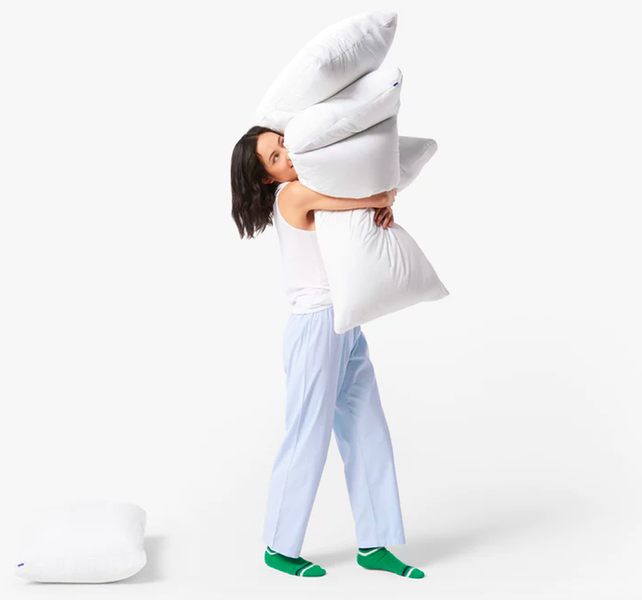 A model standing up and balancing several pillows in their arms