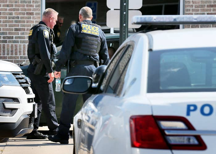 Homeland Security officers talk to a person behind the Immigration and Customs Enforcement headquarters in Grand Island, Nebraska, on Aug. 8.
